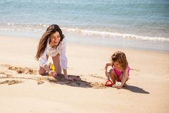 Single mom with her daughter. Happy young single mother having fun with her daughter and drawing together in the sand stock photography
