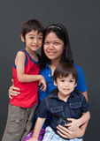 Single mom with little sibling boy. Gray background stock image