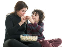 Single mom and son eating popcorn. Hispanic single mother sharing popcorn with her eight years old son. Latin family enjoying the simplicity of life. White royalty free stock image