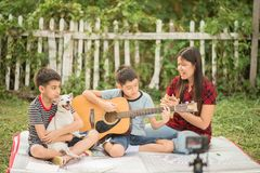 Single mom and sons play guitar together in the park. Single mom and sons play guitar together with fun in the park royalty free stock image