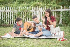 Single mom and sons play guitar together in the park. Single mom and sons play guitartogether with fun in the park stock images