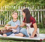 Single mom and sons play guitar together in the park. Single mom and sons play guitartogether with fun in the park royalty free stock image
