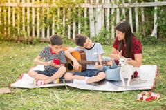 Single mom and sons play guitar together in the park. Single mom and sons play guitartogether with fun in the park stock photos