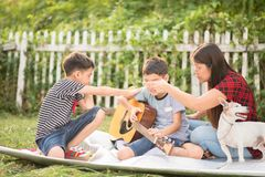 Single mom and sons play guitar together in the park. Single mom and sons play guitartogether with fun in the park royalty free stock photography