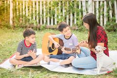 Single mom and sons play guitar together in the park stock images