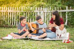 Single mom and sons play guitar together in the park royalty free stock images