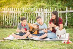 Single mom and sons play guitar together in the park. Single mom and sons play guitartogether with fun in the park royalty free stock photo