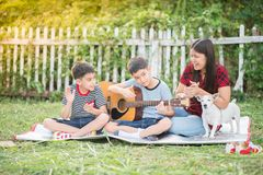 Single mom and sons play guitar together in the park royalty free stock photography