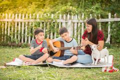 Single mom and sons play guitar together in the park. Single mom and sons play guitartogether with fun in the park stock photo