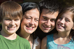 Single Mom of Teens. Smiling family portrait of a single mother and her three teenagers stock photography