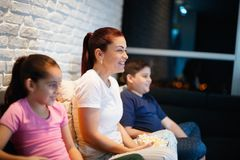 Single Mother And Children Watching TV At Night. Movie night at home with divorced mother, daughter and son. Modern family watching television and eating popcorn Royalty Free Stock Photos