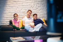 Single Mother And Children Watching TV At Night. Movie night at home with divorced mother, daughter and son. Modern family watching television and eating popcorn Stock Image