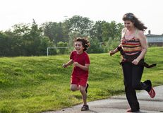 Single mother having fun with her child. Single mother running and having fun with her child in a park royalty free stock image