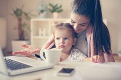 Mother and little girl at home using laptop together. stock image