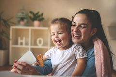 Mother and little girl taking self picture at home. Close royalty free stock photography