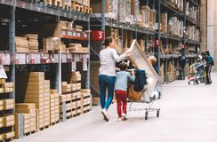 Single mother shopping at IKEA furniture store pushing cart royalty free stock photography
