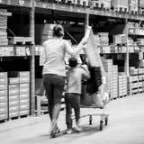 Single mother shopping at IKEA furniture store pushing cart royalty free stock photo