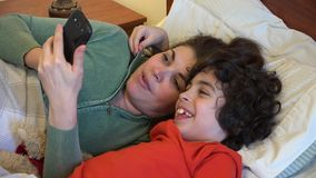 Single mother and son checking a smartphone Royalty Free Stock Photography