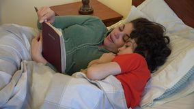 Single mother and son having a Christian devotional. Single mother reading the Bible to her son before bedtime. Daily devotional of a Christian family stock video footage