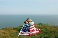 Single mother with son on independence day of USA. Woman and her child walk with the USA flag on the ocean coast. Wonam dressed in a coral dress with a denim royalty free stock images