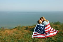 Single mother with son on independence day of USA. Woman and her child walk with the USA flag on the ocean coast. Wonam dressed in a coral dress with a denim stock photography