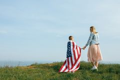 Single mother with son on independence day of USA. Woman and her child walk with the USA flag on the ocean coast. Wonam dressed in a coral dress with a denim stock photos