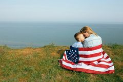 Single mother with son on independence day of USA. Woman and her child walk with the USA flag on the ocean coast. Wonam dressed in a coral dress with a denim stock image