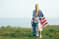 Single mother with son on independence day of USA. Woman and her child walk with the USA flag on the ocean coast. Wonam dressed in a coral dress with a denim royalty free stock image