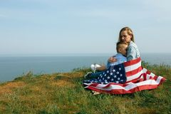 Single mother with son on independence day of USA. Woman and her child walk with the USA flag on the ocean coast. Wonam dressed in a coral dress with a denim royalty free stock photos