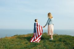 Single mother with son on independence day of USA. Woman and her child walk with the USA flag on the ocean coast. Wonam dressed in a coral dress with a denim royalty free stock photo