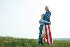 Single mother with son on independence day of USA. Woman and her child walk with the USA flag on the ocean coast. Wonam dressed in a coral dress with a denim stock images