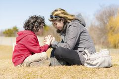 Single Mother and Son Praying Outdoors Royalty Free Stock Image