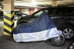 Single motorcycle is in warm underground parking garage covered with tent Stock Image