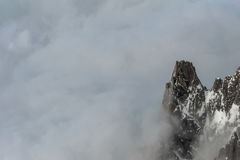 Single mountain peak emerging from thick cloud cover Stock Photo