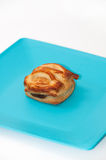 Single muffin with chocolate cream on blue plate Stock Images