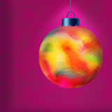 Single Multi Colored Christmas Ornament. Illuminated Over Purple Textured Wallpaper Royalty Free Stock Photo