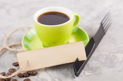 Single new black plastic comb and old blank rectangle paper with hole and long rope beside full cup of black coffee and lot of sca royalty free stock photo