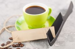 Single new black plastic comb and old blank rectangle paper with hole and long rope beside full cup of black coffee and lot of sca stock photography
