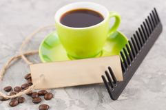 Single new black plastic comb and old blank rectangle paper with hole and long rope beside full cup of black coffee and lot of sca. Ttered coffee beans on stock photos