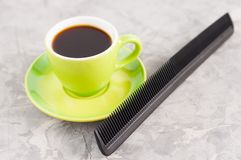 Single new plastic comb near full cup of black tasty coffee on green round ceramic saucer. On old gray broken concrete royalty free stock photo