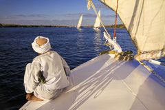 Nubian Man Sailing on Nile River in Aswan Egypt. Single Nubian Man Wearing Traditional White Desert Clothing Sitting on Felucca Boat Deck and Sailing Down the Stock Images