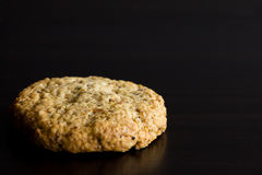Single oatmeal cookie, healthy dessert, on dark background. Copy Stock Images