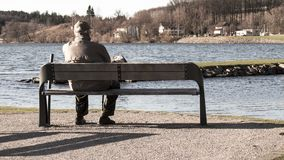 Single old man on sits on a bench stock photography