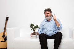 Single old men on white couch with a bonsai Royalty Free Stock Photography