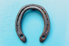Single old rustic horse shoe on blue chalk painted wooden board Royalty Free Stock Photos
