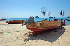 Single old wooden ship on the beach in Zanzibar. Old wooden ship with nets for catching fish on the beach in Zanzibar - Tanzania Stock Photos