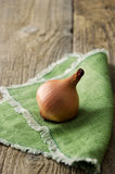 Single onion on green cloth Stock Images