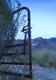 Single open gate leading to the mountains. Open rusty gate with track leading to mountains stock photo