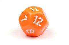 A single, orange, 12-sided die on white. Macro photo of a single, orange twelve-sided die, on white background stock photos