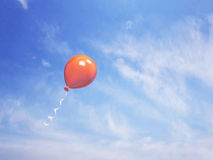 Single orange balloon in the blue sky Royalty Free Stock Photo
